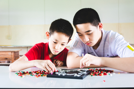 Photo pour Boys are concentrate and focus on playing lego bricks - image libre de droit