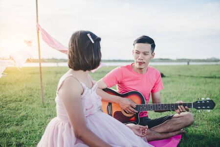 Photo pour Asian husband playing guitar and enjoy with his pregnant wife outdoor Asian Married couple and family concept. - image libre de droit