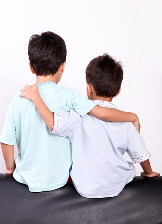 two children hugging back over white background