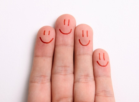 Fingers representing a family drawing happy faces on the fingertips