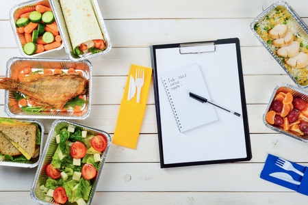 Note paper and a pen on the wooden surface. Plastic fork and a knife, fish with arugula, baby carrots, sandwich, tomato and feta salad, chicken, tangerines and plums. Counting calories.