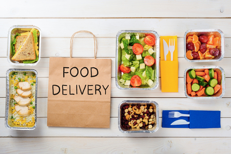 Paper bag with Food Delivery sign. Cashews, hazelnuts and dates, carrots and cucumbers, rice with chicken, sandwiches, tomato salad, plastic cutlery and fruit, wooden surface. Ordering your meal.