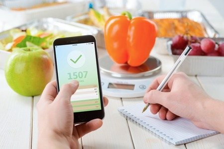 Calorie counter app on the smartphone, making notes, close-up. Grapes, an apple on the wooden surface, a pepper on the food scale on the background. Weight loss journey.