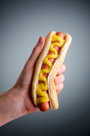Photo pour Male hand holding hot dog - image libre de droit