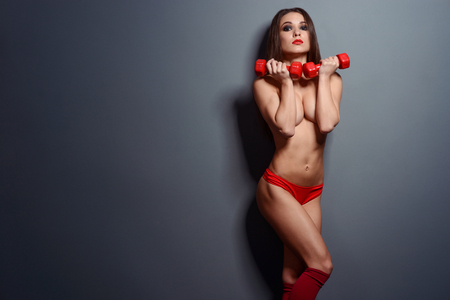 Photo for Fit sportswoman posing with dumbbells - Royalty Free Image
