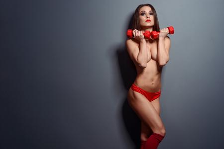 Photo pour Fit sportswoman posing with dumbbells - image libre de droit