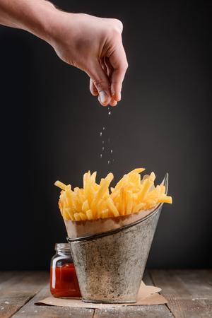 Foto de Hand sprinkles pinch of salt - Imagen libre de derechos