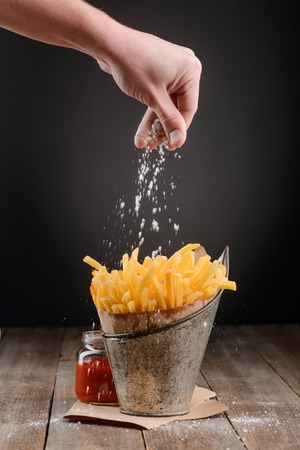 Photo pour Hand sprinkles salt on fries - image libre de droit