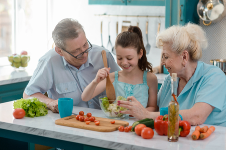 Photo pour Little girl cooking salad - image libre de droit