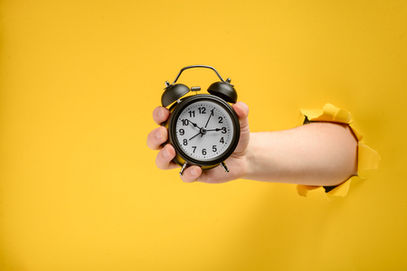 Foto per Hand holding an alarm clock - Immagine Royalty Free