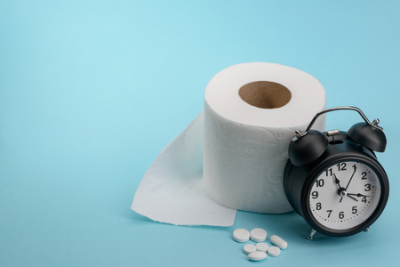 Foto de Toilet paper, pills and alarm clock on blue background. Diarhhea or constipation cure. Medical commercial concept. - Imagen libre de derechos
