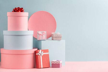 Foto de Pink and turquoise round gift boxes and red fir tree on teal background - Imagen libre de derechos