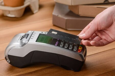 Photo pour Man paying by a contactless credit card for pizza and coffee - image libre de droit