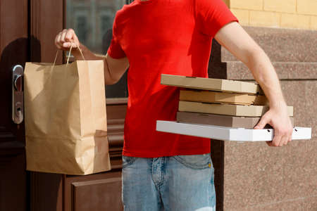 Man is holding paper bag and pizza boxes