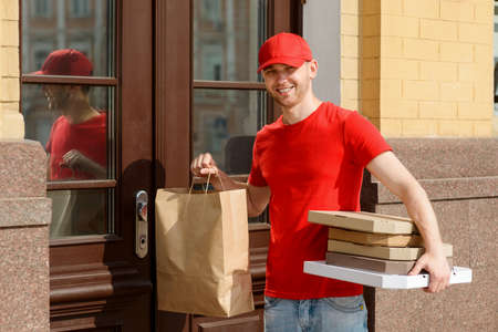Delivery man waiting for customer. Young courier at work