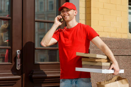 Delivery man calling to customer and holding boxes of pizza