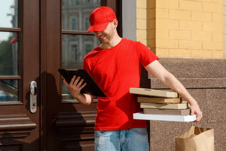 Courier waiting at the door, looking at a clipboard