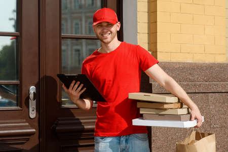 Courier is waiting for customer, holding a receipt and pizza boxes