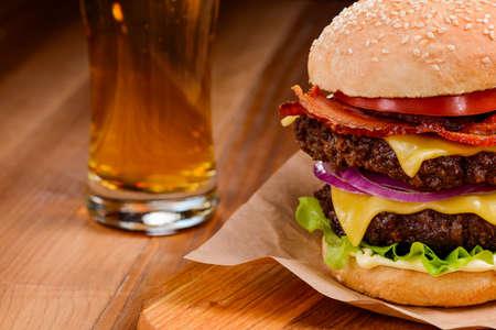 Photo pour Double hamburger and beer on a wooden table, selective focus - image libre de droit