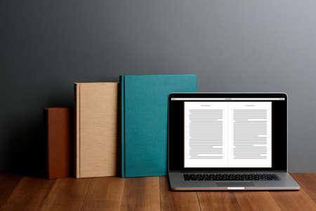 Photo pour Books and laptop with E-reader app on desktop - image libre de droit