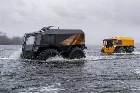 Foto de Two all-terrain vehicles crossing a river on a clody day - Imagen libre de derechos
