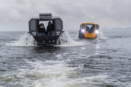 Foto de Two all-terrain vehicles driving in the river on a cloudy day - Imagen libre de derechos