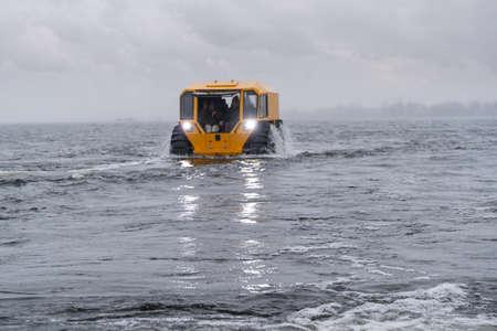 Foto de Yellow off-road vehicle sailing in the river - Imagen libre de derechos