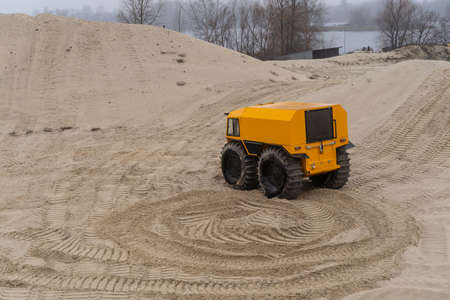 Foto de Yellow all-terrain vehicle driving and leaving twisted marks in the sand - Imagen libre de derechos
