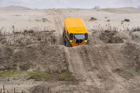 Foto de Yellow all-terrain vehicle touring through sandy hills - Imagen libre de derechos