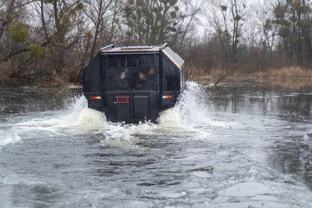 Foto de All-terrain vehicle with passengers crossing an icy river - Imagen libre de derechos
