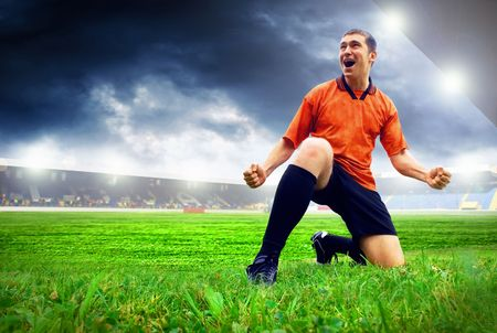 Photo pour Happiness football player after goal on the field of stadium with blue sky - image libre de droit