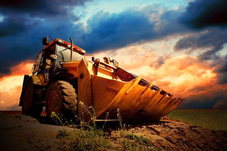 Photo for Yellow tractor on golden surise sky - Royalty Free Image