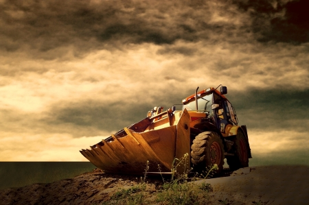 Photo pour Yellow tractor on golden sunrise sky - image libre de droit