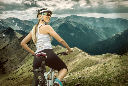 Beautiful woman in helmet and glasses stay on the bicycle around mountains.の写真素材