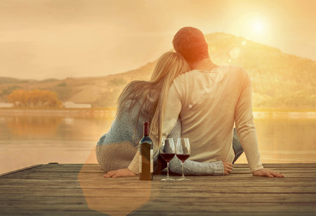 Photo pour Romantic Couple sitting on the pier with red wine. - image libre de droit