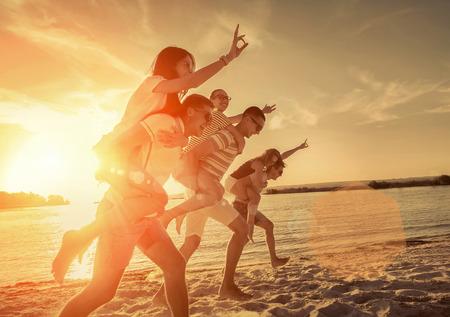 Foto de Friends fun on the beach under sunset sunlight. - Imagen libre de derechos