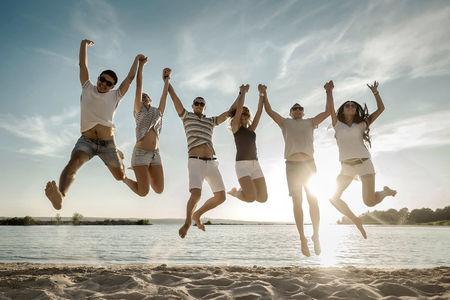 Photo pour Friends jumping on the beach under sunset sunlight. - image libre de droit