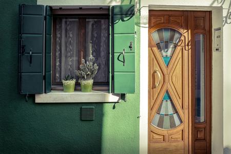 Beautiful  view window with flower and door. Burano island Venice.