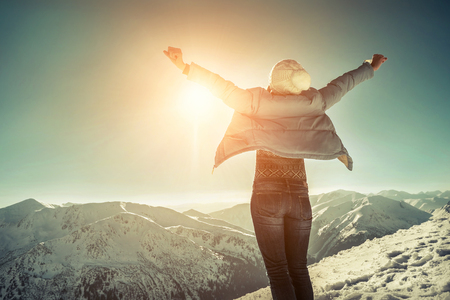 Foto de Happy woman relaxing on the top of mountain under blue sky with sunlight at sunny winter day, travel vacation, landscape mountains background. - Imagen libre de derechos