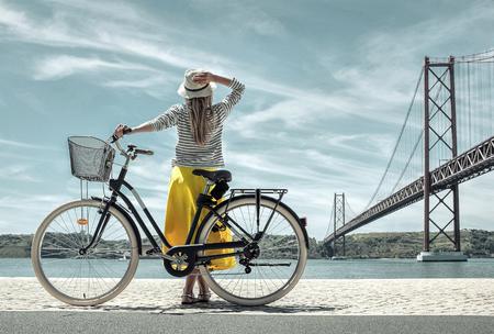 Foto de Blonde woman in summer hat and yellow skirt with her city bicycle walking coastline near the bridge under sunlight in sunny summer day. - Imagen libre de derechos