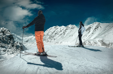 Men and Woman on the ski before sport action at sunny day around mountains under blue sky.の写真素材