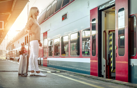 Foto de Blonde woman with her luggage stay near the red train on the peron os rail station under sun light at sunny day. - Imagen libre de derechos