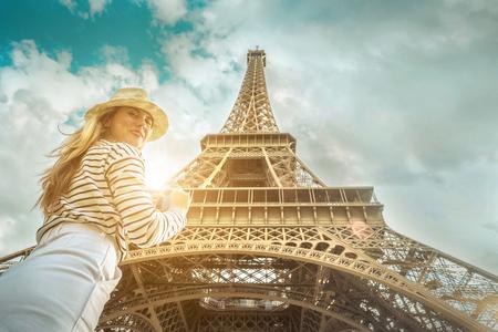Photo pour Woman tourist selfie near the Eiffel Tower in Paris under sunlight and blue sky. Famous popular touristic place in the world. - image libre de droit