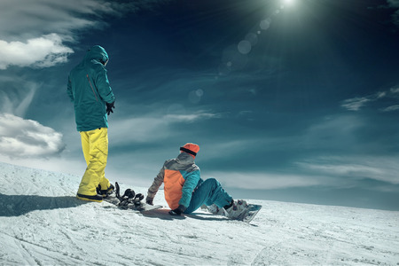 Men and Woman on the snowboards before sport action at sunny day around mountains under blue sky.の写真素材
