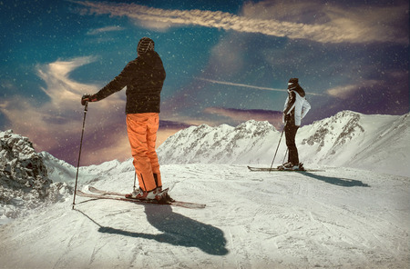 Photo pour Men and Woman on the ski before sport action at sunny day around mountains under blue sky. - image libre de droit