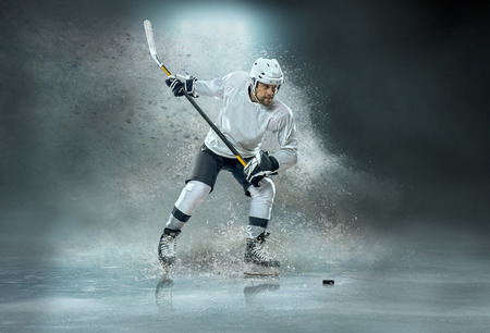 Photo pour Caucassian ice hockey Players in dynamic action in a professional sport game play on the laptop in hockey under stadium lights. - image libre de droit