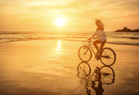 Photo pour Happiness woman traveler with her bicycle rides on sea coastline and looking on beautifull sunset sky in sunny summer day on beach. Freedom, Travell, Journej,  concept. - image libre de droit
