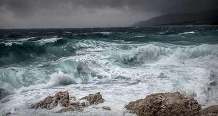 Photo pour Stormy sea view  near coastline at evening time. Waves, splashed drops under dark dramatic sky. - image libre de droit