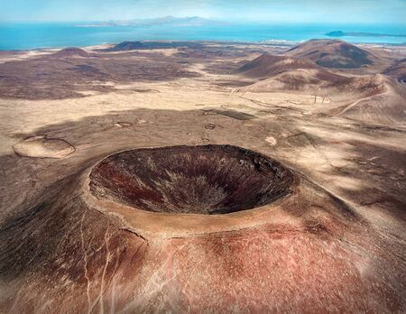 Photo pour Beautiful panoramic birds eye view on Calderon Hondo, Fuerteventura island. Aerial shooting vulcano around mountains with ocean coastline at sunny day. Travell, Mountains,islands, nature, freedom concept. - image libre de droit