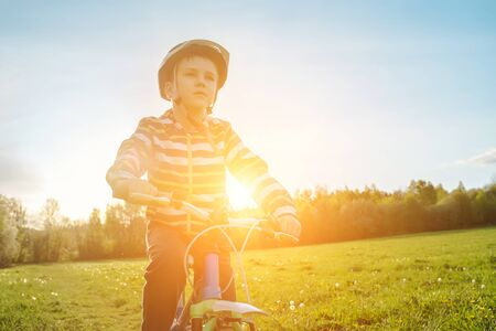 Photo pour Child on bike in park. Boy going wearing safe bicycle helmets. Little Kid biking on sunny summer day. Active healthy outdoor sport Fun activity. - image libre de droit